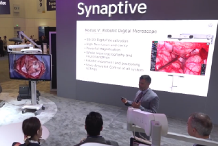 surgeon presenting in front of large screen